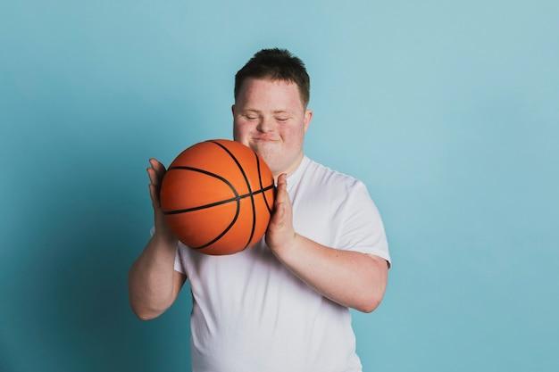 Simpatico ragazzo atletico con sindrome di down che tiene in mano un pallone da basket