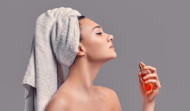 La ragazza carina e attraente con un asciugamano in testa usa il profumo isolato su uno sfondo grigio. concetto di cura della pelle. trattamenti termali, cosmetologia, trucco.