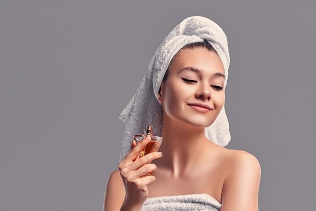 La ragazza carina e attraente con un asciugamano in testa usa il profumo isolato su uno sfondo grigio. concetto di cura della pelle.