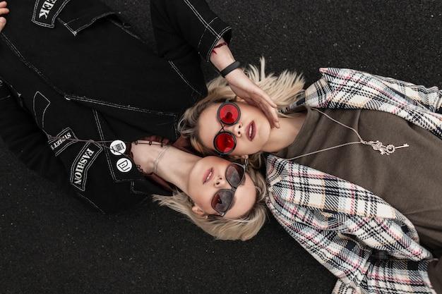 Lesbiche carine e attraenti in abbigliamento casual alla moda in occhiali eleganti per giovani che riposano sulla strada