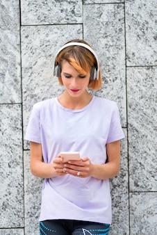 Carino attraente donna matura che ascolta la musica sul suo telefono cellulare utilizzando le cuffie stereo