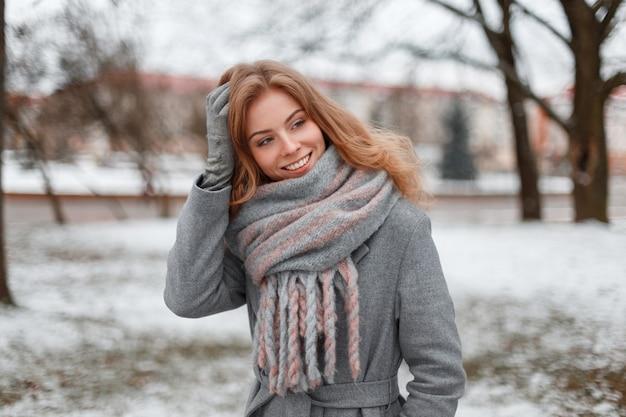 Carina attraente bella giovane donna in guanti grigi in un cappotto grigio alla moda con una sciarpa lavorata a maglia vintage è in piedi e sorridente in un parco innevato