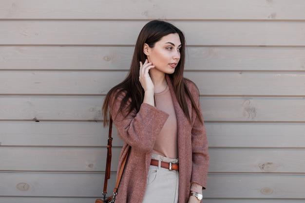 Modello di moda carino giovane donna attraente in eleganti vestiti marroni con borsa di moda in pelle in posa vicino edificio in legno d'epoca sulla strada. ragazza abbastanza fine in abbigliamento casual all'aperto. signora di bellezza.