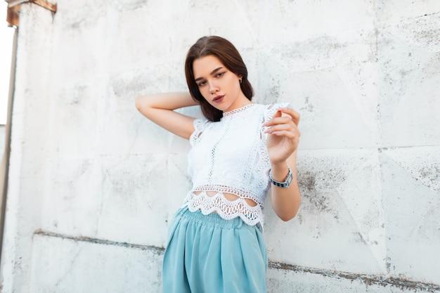 La giovane donna attraente sveglia raddrizza i capelli. elegante bella ragazza in top in pizzo alla moda in pantaloni blu alla moda pone sulla strada vicino al muro vintage. nuova collezione di abbigliamento donna estivo.
