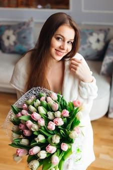 Giovane donna carina e attraente con un bellissimo grande mazzo di fiori ai tulipani. buona festa della mamma! mattina perfetta.
