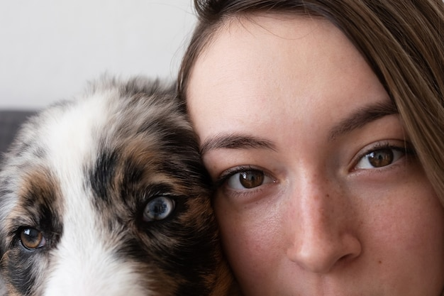 Carino pastore australiano blue merle cucciolo di cani occhi vicino al viso della donna. occhi di diversi colori. guardando la fotocamera. adozione. riparo. concetto amichevole e di cura degli animali domestici.