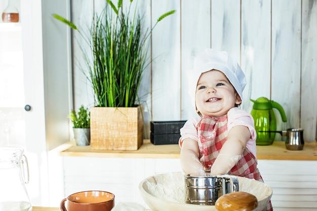 Ragazza carina con un berretto e un grembiule felice e bello che prepara pasticceria e farina in cucina a casa