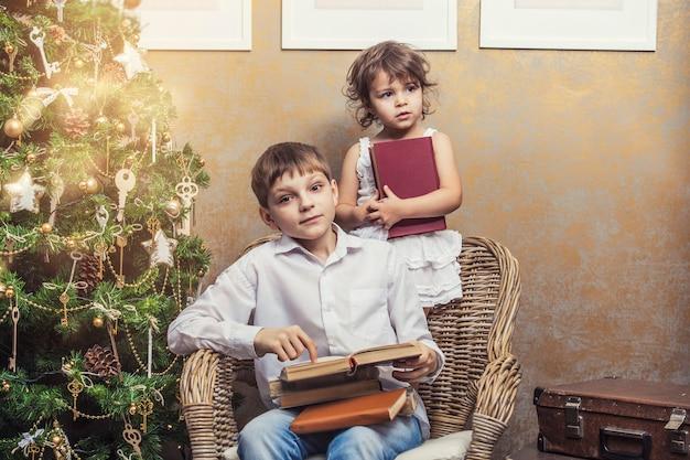 Bambini carini ragazzo e ragazza su una sedia che leggono un libro in un interno retrò di natale