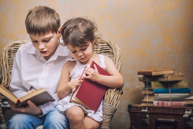 Bambini carini ragazzo e ragazza su una sedia che leggono un libro in un interno vintage