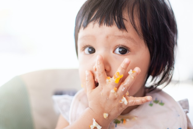 Ragazza carina bambino asiatico bambino mangiare cibo sano da sola e fare un casino