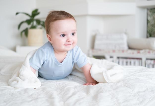 Neonato sveglio di 6 mesi in tuta blu sorridente e sdraiato sul letto con un plaid bianco a casa.