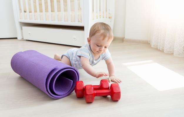 Neonato sveglio che striscia sul pavimento e gioca con i manubri