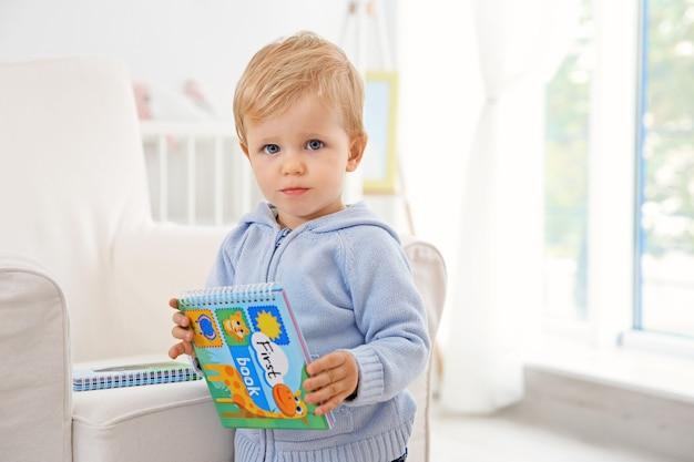 Neonato sveglio che tiene un libro