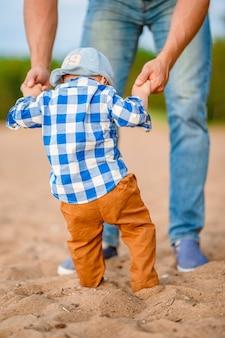 Il neonato carino impara a camminare tenendo le mani di papà sulla spiaggia sulla sabbia