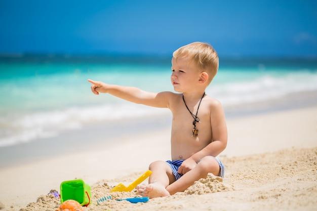 Il neonato sveglio che gioca con la spiaggia gioca sulla spiaggia tropicale
