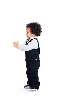 Neonato sveglio. vista laterale del piccolo bambino africano che guarda lontano con un sorriso mentre sta in piedi su sfondo bianco