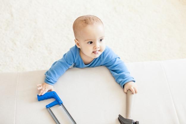 Simpatico bambino in piedi vicino al divano, tiene il martello e intende lavorare