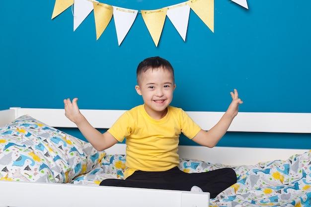 Neonato sveglio con sindrome di down sul letto nella camera da letto di casa