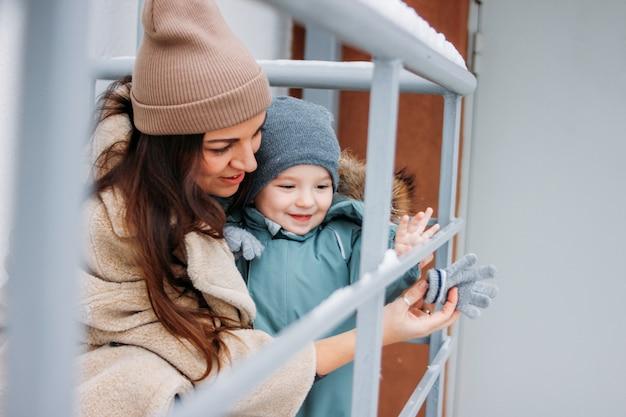 Il neonato sveglio con la madre esplora il mondo nella stagione invernale