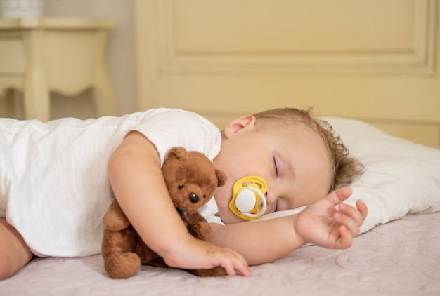 Neonato sveglio con il capezzolo che dorme sul letto a casa bambino che abbraccia l'orsacchiotto