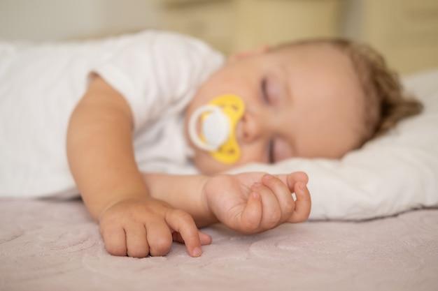Neonato sveglio con il capezzolo che dorme sul letto a casa. messa a fuoco selettiva sulle mani.