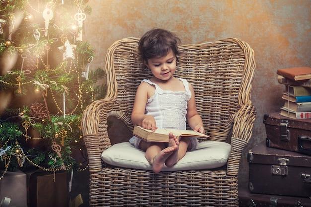 Bambino carino su una sedia che legge un libro in un interno retrò di natale Foto Premium