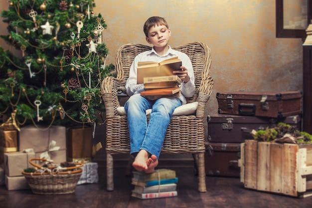 Bambino carino su una sedia che legge un libro in un interno retrò di natale