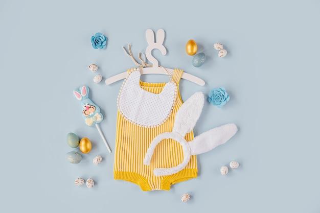 Simpatico costume da coniglietto pasquale. body in maglia con soffici orecchie da coniglio, uova di pasqua e caramelle su sfondo blu. concetto di vacanza. disposizione piatta, vista dall'alto
