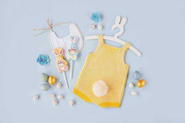 Simpatico costume da coniglietto pasquale. body lavorato a maglia con coniglio soffice coda, uova di pasqua e caramelle su sfondo blu. concetto di vacanza. disposizione piatta, vista dall'alto
