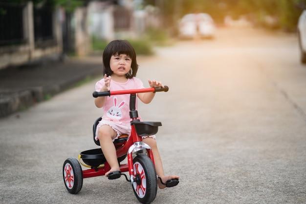 Bambino carino che piange e va in bicicletta