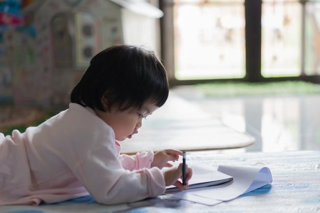 Bambino sveglio che disegna sul taccuino sul pavimento