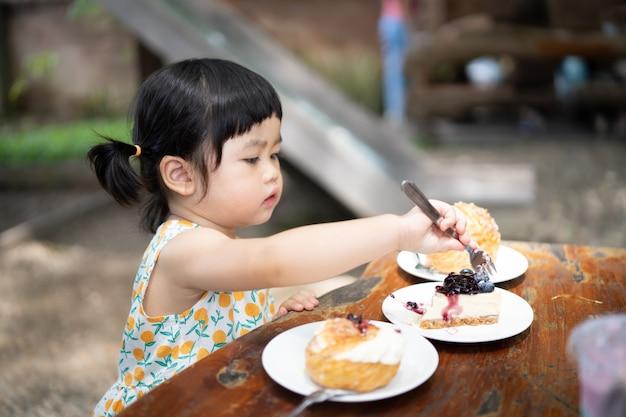 Bambino carino che mangia la torta e si siede sul tavolo al bar