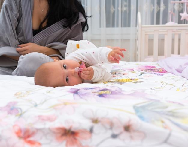 Un bambino carino amoreggiare sul letto diffuso con la madre al mattino.