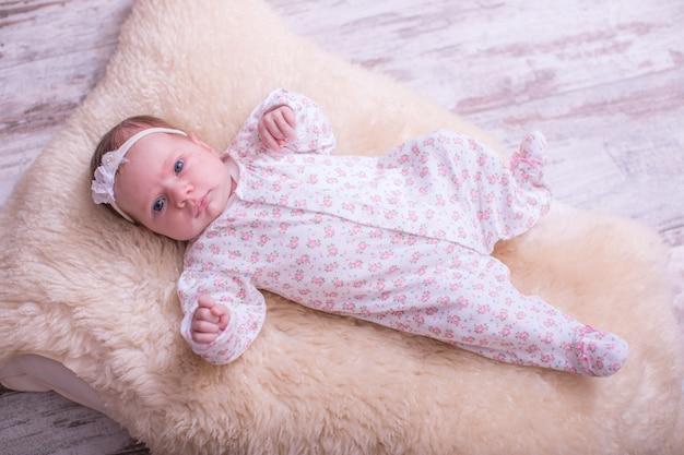Neonata sveglia a letto a casa con un orsacchiotto