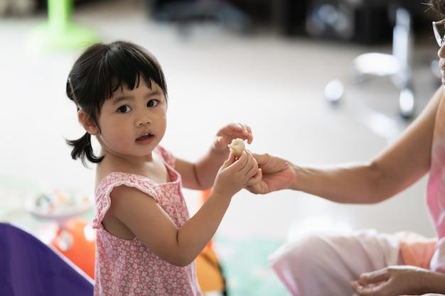 Bambina carina che mangia i biscotti in casa con sua nonna