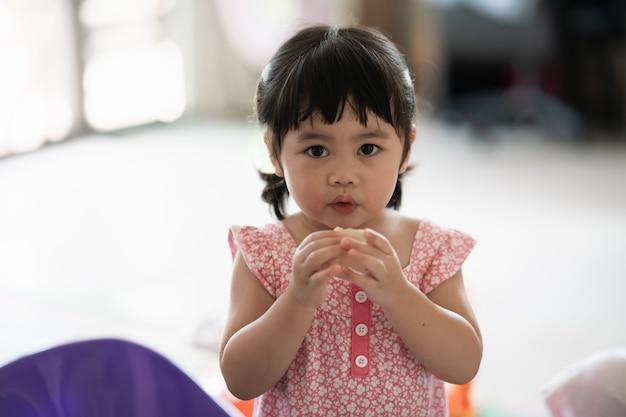 Bambina carina che mangia i biscotti in casa