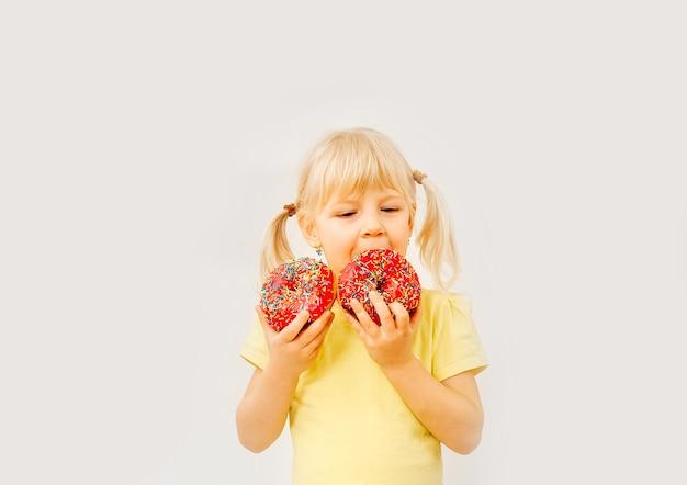 Neonata sveglia che mangia ciambelle dolci su uno sfondo chiaro.