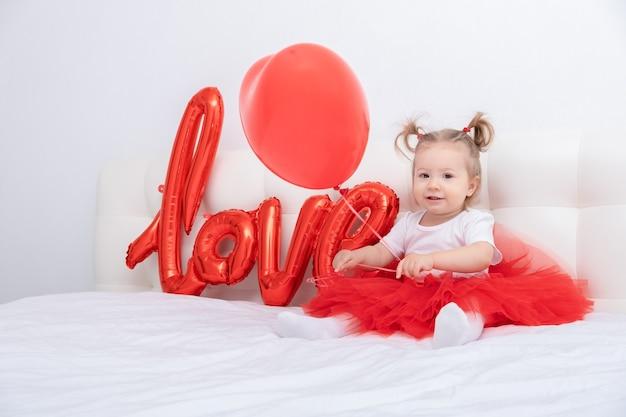 La neonata sveglia tiene la scritta amore da palloncini su fogli bianchi
