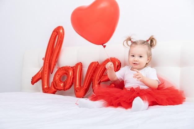 La neonata sveglia tiene la scritta amore da palloncini su un muro bianco.