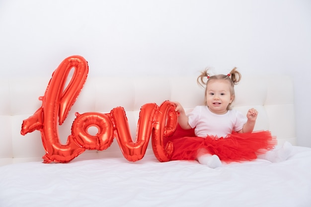 La neonata sveglia tiene la scritta amore da palloncini