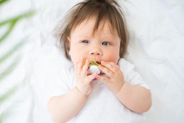Mese carino della neonata con il capezzolo sdraiato su un letto bianco a casa vista dall'alto