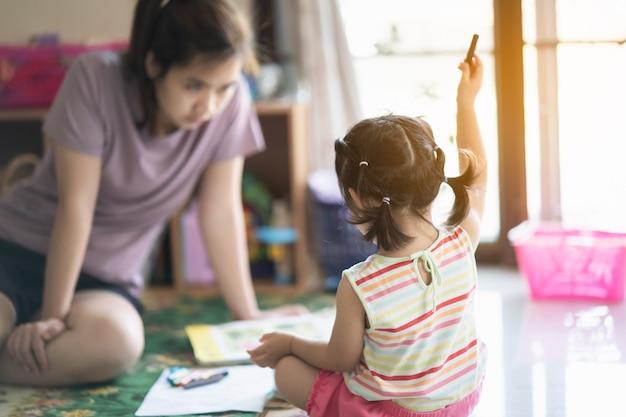 Bambina carina che dipinge con sua madre a casa