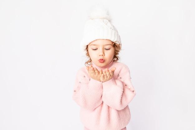 Neonata sveglia in abiti invernali rosa su sfondo bianco soffia via le sue mani, spazio per il testo