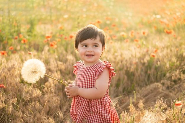 Neonata sveglia in vestito rosso che tiene grande dente di leone sul campo dei papaveri al tramonto estivo.