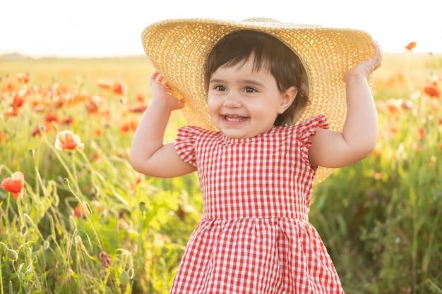 Neonata sveglia in vestito rosso e cappello di paglia sul campo dei papaveri al tramonto di estate.