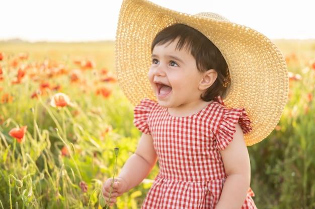 Neonata sveglia in vestito rosso e cappello di paglia che tiene fiore sul campo dei papaveri al tramonto estivo