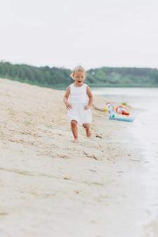 Neonata sveglia che corre e che si diverte sulla spiaggia vicino al lago. il concetto di vacanza estiva. giorno del bambino. famiglia trascorrere del tempo insieme sulla natura.