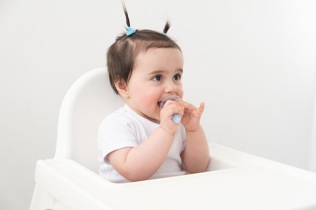 Neonata sveglia che sorride e che pulisce i suoi denti con un pennello colorato