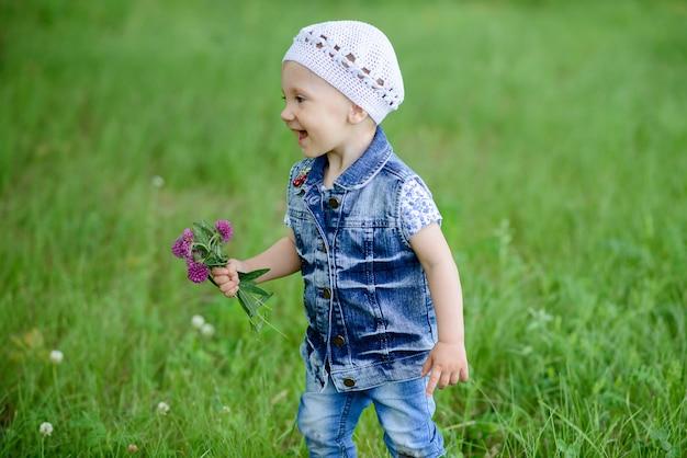 Neonata sveglia che cammina nel bellissimo parco con fiori colorati nella stagione estiva ha sorridente e felice in piedi sfondo natura all'aperto.