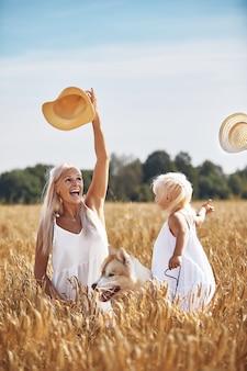 Neonata sveglia con mamma e cane sul campo di grano giovane famiglia felice godersi il tempo insieme alla natura mamma, piccola neonata e cane husky che riposa insieme all'aperto, amore, concetto di felicità.